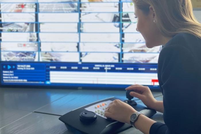 Das Bild zeigt eine Frau vor einer Videoanlage
