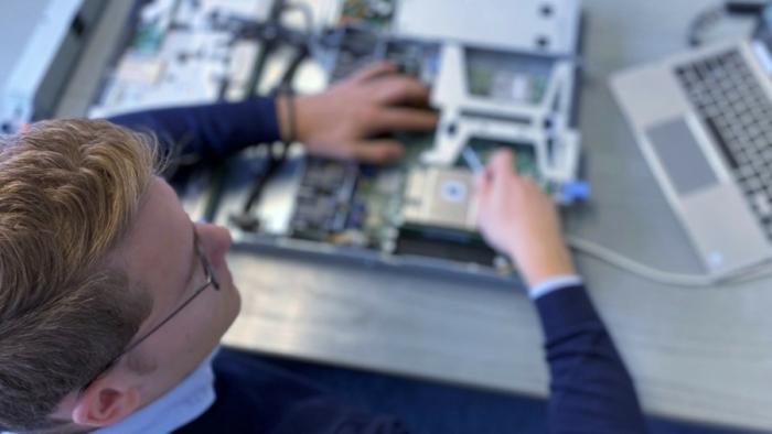 Das Bild zeigt einen Mann der einen Server repariert